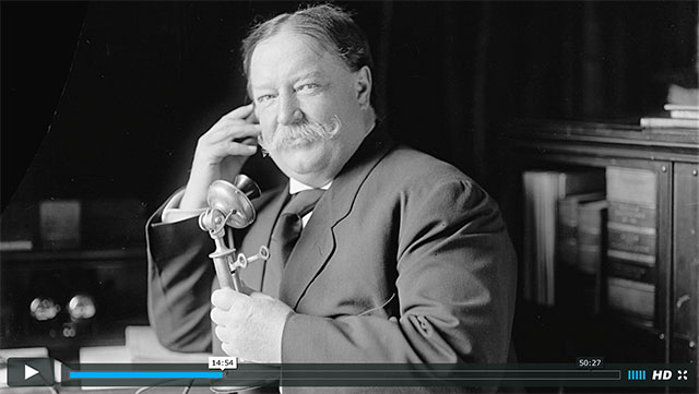 A screenshot from a video of Howard Taft talking on the telephone