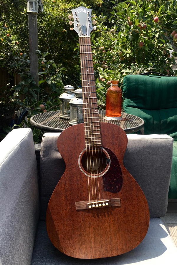 The guitar seated on porch furniture.