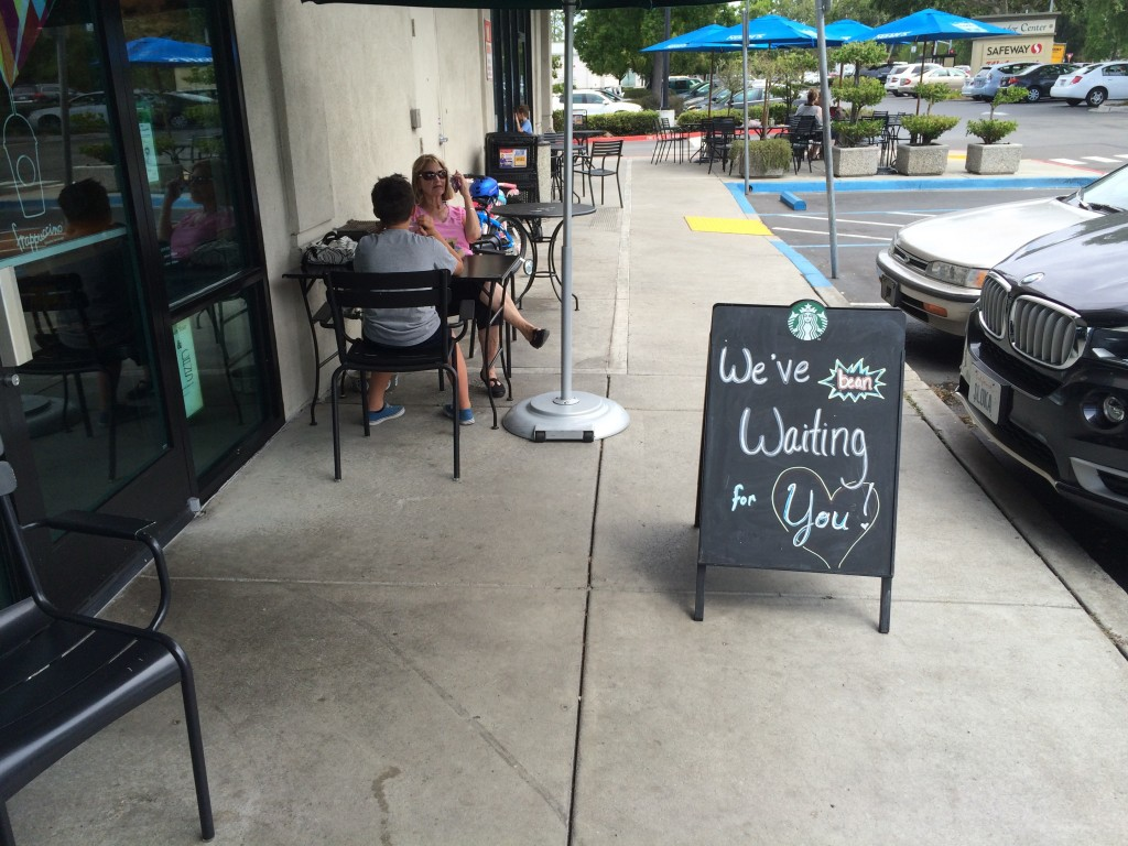 A Starbucks sign blocks the side walk