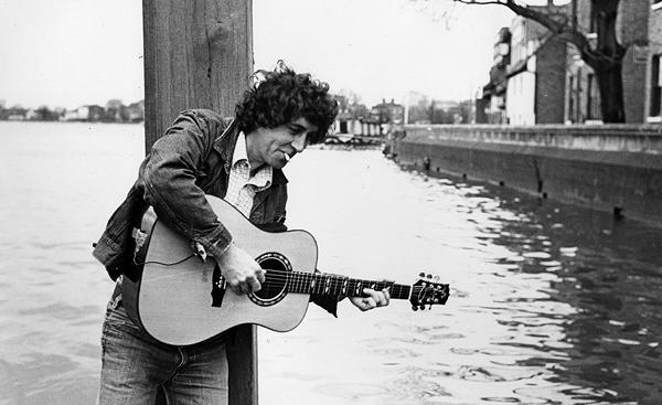 Bert Jancsh standing playing guitar by the water with a cigarette hanging from his lips.