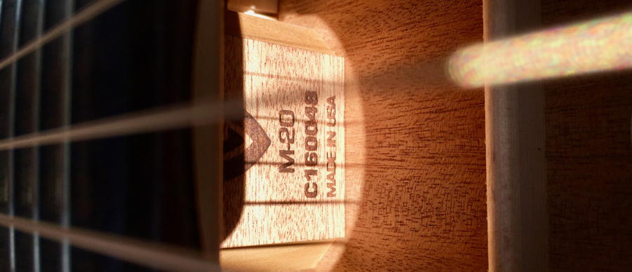 Looking in the sound hole of the guitar to see the serial number.